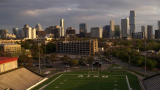DX0002_105_007 - 5.7K stock footage aerial video fly over football stadium, approach office buildings and skyscrapers at sunset in Downtown Austin, Texas