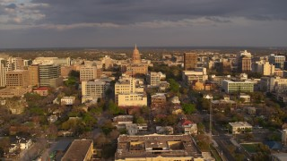 DX0002_105_014 - 5.7K stock footage aerial video Texas State Capitol dome and office buildings at sunset before descent in Downtown Austin, Texas