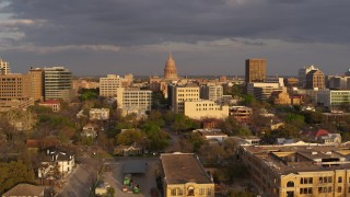 DX0002_105_016 - 5.7K stock footage aerial video Texas State Capitol dome seen while descending near office buildings at sunset in Downtown Austin, Texas