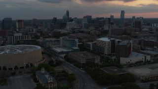 DX0002_105_017 - 5.7K stock footage aerial video approach hospital with skyscrapers in the background at sunset in Downtown Austin, Texas