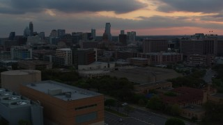 DX0002_105_020 - 5.7K stock footage aerial video office buildings and capitol dome at sunset, skyscrapers in background in Downtown Austin, Texas