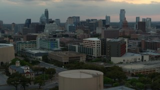 DX0002_105_021 - 5.7K stock footage aerial video ascend for view of hospital, skyscrapers and capitol dome at sunset in Downtown Austin, Texas