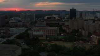 DX0002_105_031 - 5.7K stock footage aerial video of ascending by the university campus with setting sun in distance, Austin, Texas