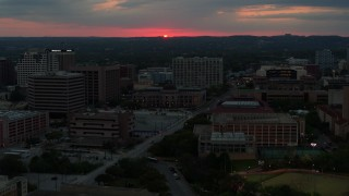 DX0002_105_034 - 5.7K stock footage aerial video stationary view of setting sun before flying by university campus, Austin, Texas