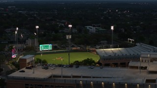 DX0002_105_037 - 5.7K stock footage aerial video of ascending by baseball stadium at the University of Texas at twilight, Austin, Texas