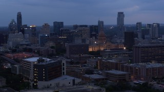 DX0002_105_041 - 5.7K stock footage aerial video a view of office buildings around capitol at twilight, skyscrapers in background in Downtown Austin, Texas