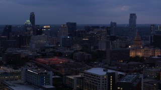 DX0002_105_046 - 5.7K stock footage aerial video of approaching office buildings, capitol and skyscrapers at twilight in Downtown Austin, Texas