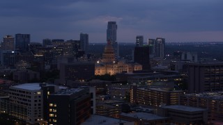 DX0002_105_050 - 5.7K stock footage aerial video ascend near office buildings, capitol and skyscrapers at twilight in Downtown Austin, Texas