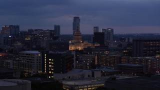 DX0002_105_052 - 5.7K stock footage aerial video descend near office buildings with view of state capitol at twilight in Downtown Austin, Texas