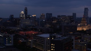 DX0002_105_054 - 5.7K stock footage aerial video descend with view of office buildings, skyscrapers near capitol at twilight in Downtown Austin, Texas