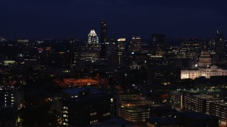 DX0002_106_004 - 5.7K stock footage aerial video of passing by office buildings, skyscrapers and capitol at night in Downtown Austin, Texas