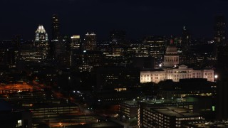 DX0002_106_011 - 5.7K stock footage aerial video of skyscrapers and office buildings behind the Texas State Capitol at night in Downtown Austin, Texas