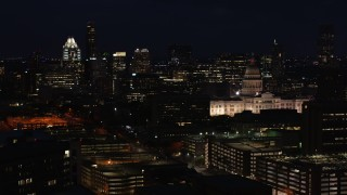 DX0002_106_012 - 5.7K stock footage aerial video flyby skyscrapers and office buildings behind Texas State Capitol at night in Downtown Austin, Texas
