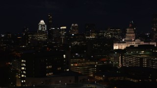 DX0002_106_014 - 5.7K stock footage aerial video ascend with view of skyscrapers, office buildings, Texas State Capitol at night in Downtown Austin, Texas