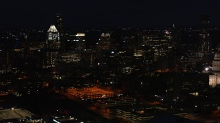 DX0002_106_015 - 5.7K stock footage aerial video slowly fly toward skyscrapers and office buildings at night in Downtown Austin, Texas