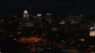 DX0002_106_016 - 5.7K stock footage aerial video slowly descend past skyscrapers and office buildings at night in Downtown Austin, Texas