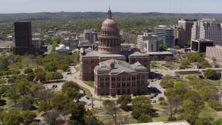 DX0002_107_009 - 5.7K stock footage aerial video descend by the side of Texas State Capitol and grounds in Downtown Austin, Texas