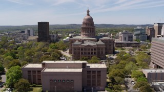 DX0002_107_019 - 5.7K stock footage aerial video reverse view of Texas State Capitol, reveal library in Downtown Austin, Texas