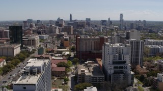 DX0002_107_041 - 5.7K stock footage aerial video ascend from the University of Texas for view of skyline of Downtown Austin, Texas