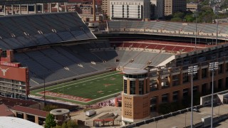 DX0002_108_025 - 5.7K stock footage aerial video ascend to focus on the empty football stadium at the University of Texas, Austin, Texas
