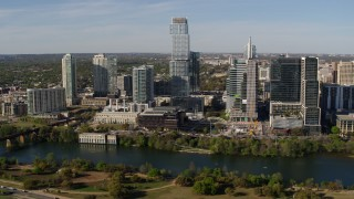 DX0002_109_005 - 5.7K stock footage aerial video modern skyscraper across Lady Bird Lake, Downtown Austin, Texas
