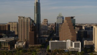 DX0002_109_034 - 5.7K stock footage aerial video reveal the state capitol while flying between skyscrapers in Downtown Austin, Texas