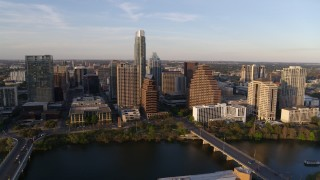 DX0002_110_004 - 5.7K stock footage aerial video of waterfront skyscrapers across Lady Bird Lake at sunset in Downtown Austin, Texas