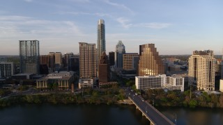 DX0002_110_006 - 5.7K stock footage aerial video of a view of waterfront skyscrapers across Lady Bird Lake at sunset in Downtown Austin, Texas