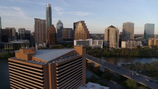 DX0002_110_007 - 5.7K stock footage aerial video fly away from waterfront skyscrapers across Lady Bird Lake at sunset, reveal hotel in Downtown Austin, Texas