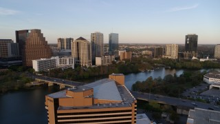 DX0002_110_008 - 5.7K stock footage aerial video fly over hotel toward waterfront skyscrapers and Lady Bird Lake at sunset, Downtown Austin, Texas