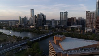 DX0002_110_009 - 5.7K stock footage aerial video fly away from skyline and Lady Bird Lake at sunset, reveal hotel in Downtown Austin, Texas