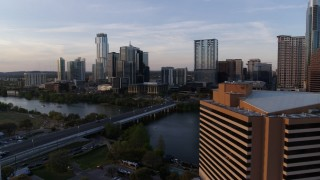 DX0002_110_010 - 5.7K stock footage aerial video flyby hotel to approach skyline and Lady Bird Lake at sunset, Downtown Austin, Texas