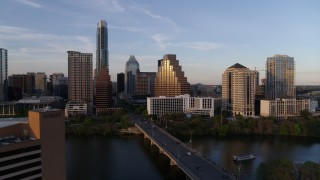 DX0002_110_014 - 5.7K stock footage aerial video approach bridge and skyline across Lady Bird Lake at sunset in Downtown Austin, Texas