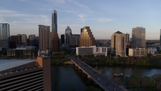 DX0002_110_015 - 5.7K stock footage aerial video fly away from skyline, and bridge over Lady Bird Lake at sunset in Downtown Austin, Texas