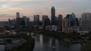 DX0002_110_017 - 5.7K stock footage aerial video of ascending over Lady Bird Lake toward the skyline at sunset in Downtown Austin, Texas