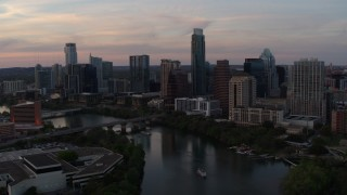 DX0002_110_018 - 5.7K stock footage aerial video of a reverse view of the skyline from over Lady Bird Lake at sunset in Downtown Austin, Texas