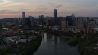 DX0002_110_019 - 5.7K stock footage aerial video of flying away from the skyline from over Lady Bird Lake at sunset in Downtown Austin, Texas