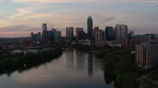 DX0002_110_021 - 5.7K stock footage aerial video slowly fly over Lady Bird Lake toward the city's skyline at sunset in Downtown Austin, Texas