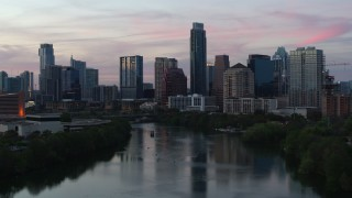 DX0002_110_026 - 5.7K stock footage aerial video slowly approaching city skyline by Lady Bird Lake at twilight in Downtown Austin, Texas