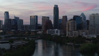 DX0002_110_027 - 5.7K stock footage aerial video a stationary view of city skyline by Lady Bird Lake at twilight in Downtown Austin, Texas
