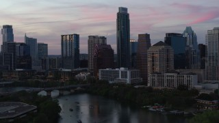 DX0002_110_028 - 5.7K stock footage aerial video focus on The Austonian in city skyline during allow approach from Lady Bird Lake at twilight in Downtown Austin, Texas