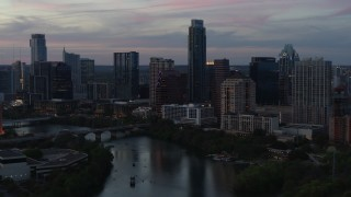 DX0002_110_030 - 5.7K stock footage aerial video of The Austonian towering over city skyline beside Lady Bird Lake at twilight in Downtown Austin, Texas