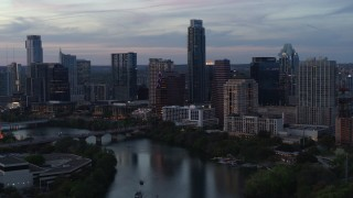 DX0002_110_031 - 5.7K stock footage aerial video of The Austonian and city skyline seen from Lady Bird Lake at twilight in Downtown Austin, Texas