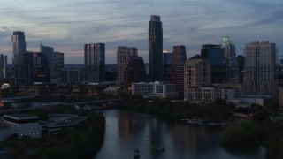 DX0002_110_034 - 5.7K stock footage aerial video of tall Austonian and city skyline seen during pass over Lady Bird Lake at twilight in Downtown Austin, Texas