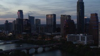 DX0002_110_036 - 5.7K stock footage aerial video approach bridge and skyscrapers by Lady Bird Lake at twilight in Downtown Austin, Texas