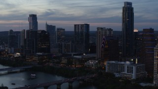 DX0002_110_037 - 5.7K stock footage aerial video reverse view of skyscrapers by Lady Bird Lake and bridge at twilight in Downtown Austin, Texas