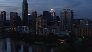 DX0002_110_040 - 5.7K stock footage aerial video approach San Jacinto Center beside Lady Bird Lake at twilight in Downtown Austin, Texas