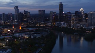 DX0002_110_046 - 5.7K stock footage aerial video fly over Lady Bird Lake, view of Congress Avenue Bridge and skyline at twilight in Downtown Austin, Texas