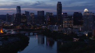 DX0002_110_048 - 5.7K stock footage aerial video reveal Lady Bird Lake and Congress Avenue Bridge, focus on skyline at twilight in Downtown Austin, Texas