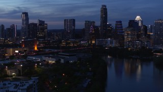 DX0002_110_049 - 5.7K stock footage aerial video descend by Lady Bird Lake, focus on skyline at twilight in Downtown Austin, Texas